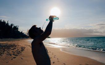 człowiek pije wodę na plaży